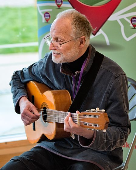 Tom Veasey singing a song on his guitar for visitors at the Rushmere pop up library before the lockdown