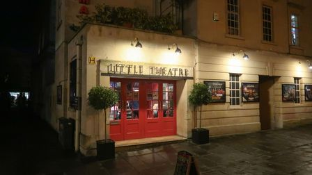 A night time picture of the doors to Little Theatre Cinema which is lit warmly by spotlights