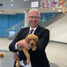 Hitchin Boys' School's headFergal Moane with one of the eight week old puppies that visited the school this week