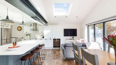 The kitchen-dining room with central island with breakfast bar and table and chairs and bi-folding doors