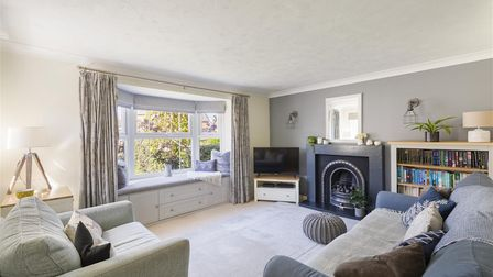 A living room with one grey, one cream wall with picture window, modern fireplace, sofas, TV and sideboard.