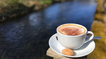 Cup of coffee by the river