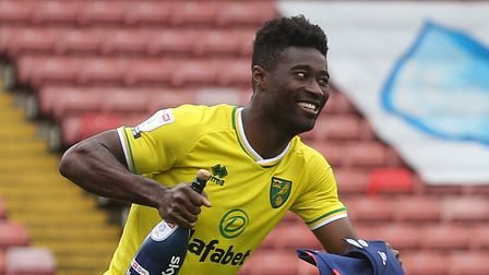 Backroom staff and players applaud and cheer Alexander Tettey of Norwich as he collects his medal at