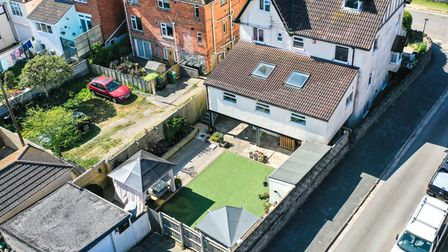 aerial view of large three-level white rendered house in Links Road, Uphill, with garden