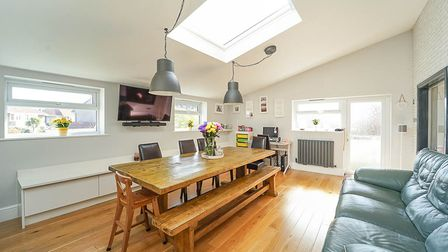 open-plan dining-family room with roof window, door at back and two windows, dining table and sofa