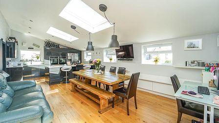 open-plan kitchen-dining-family room with table and chairs, sofa, roof windows, side windows and kitchen in back