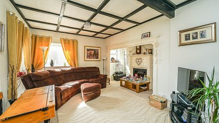 sitting room with beamed ceiling, white walls, window at back with sofa in front inset fireplace and TV on shelf unit.