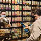 Romford BID director Julie Frost using the RM1 Club app at Mr Simms Olde Sweet Shoppe in Quadrant Arcade.