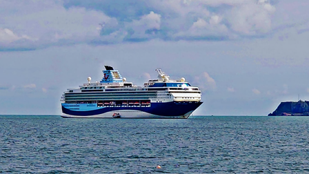A large cruise ship sits just off the coast