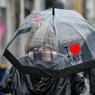 A woman walks past the shops in Porthcawl, Wales, during a heavy downpour. Picture date: Saturday Ma