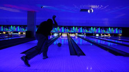 a man throws a bowling ball down a lane towards pins, the lights are low with a blue tinge
