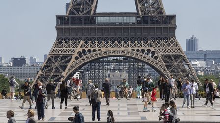 People stroll at Trocadero square next to the Eiffel Tower in Paris. (AP Photo/Michel Euler)