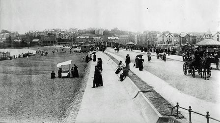 A view ofPaigntonbeach with bathing machines, bicycles and horse drawn vehicles from the Tully Collection (PR10126)