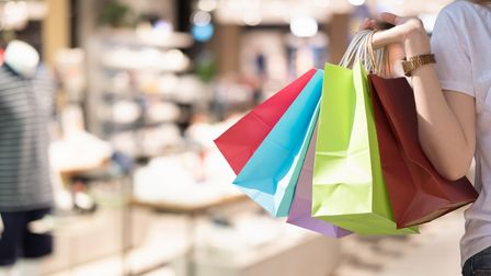Young woman with shopping bags over shopping mall background - happiness, consumerism, sale season c