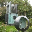 Two Barbara Hepworth statues in a garden. One is a hollow sphere, the other is made of stacked squares with holes in them.