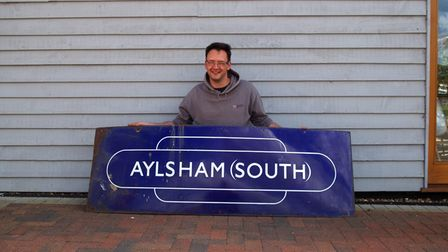 Diss Auction Roomsauctioneer, steam train driver andRailwayana specialist, Dan Woods, with the railway station sign.
