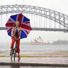 Liz Truss poses with a union flag umbrella as she takes visits Syndey to promote post-Brexit Britain