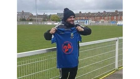 Shaun Potter holding a Wells City shirt after being announced their new manager