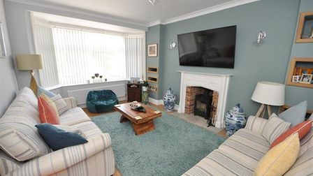 The sitting room with bay window and log burner