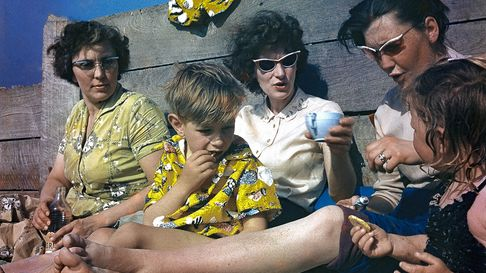 A young family relax by the beach in 1959