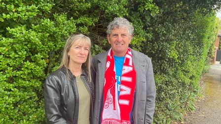A woman and a man in an Arsenal scarf