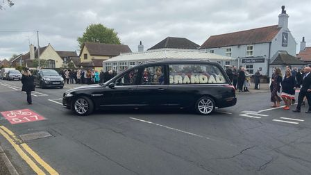 A hearse driving down the street with 'Grandad' bouquet in the back