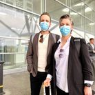 Two people wearing masks outside London Stansted