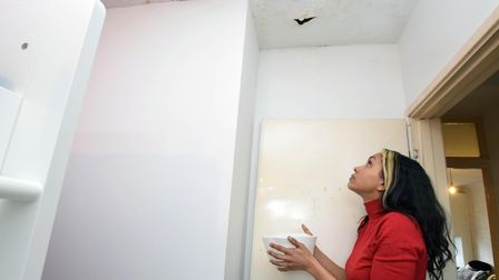 Jasmine catching water that leaks through the ceiling in her daughter's bedroom