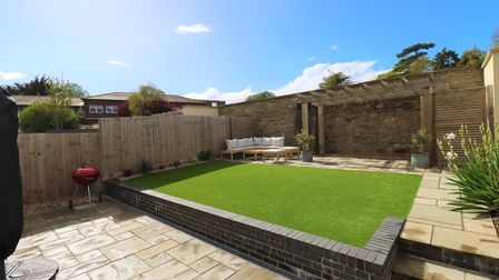 Back garden of the house in Salisbury Grove, Clevedon has artificial turf lawn, surrounded by patio and a pergola behind.