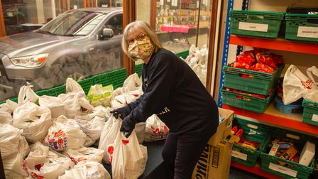A volunteer by a crate of food parcels.