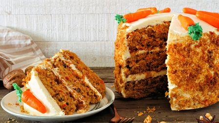 Slice of homemade carrot cake with cream cheese frosting and fondant carrots. Side view table scene