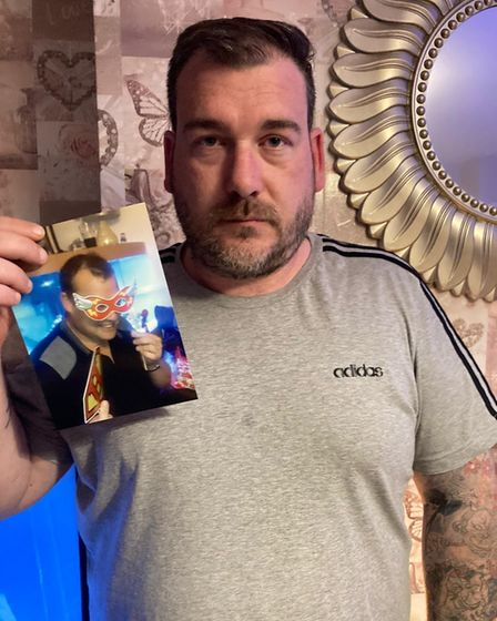 Rob Hill holding a photo of brother Ken Hill