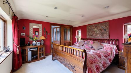 A bedroom in the cottage in Cheddar Road, Axbridge, with brightly-colouredMiddle Eastern-inspired decor including red walls