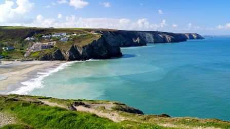 A stunning seascape view over the cliffs and across the beach in beautiful Porthtowan, Cornwall on s
