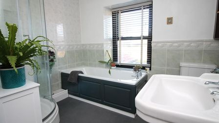 Bathroom in the house in Station Road, Congresbury, with white suite, black-panelled bath, shower, basin and cabinet.