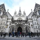 Members of the press wait outside the Royal Courts of Justice, in central London, ahead of the first