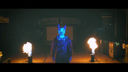 Promo shot of a scary clown by fire.