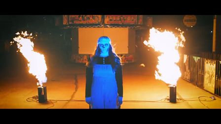 Promo shot for Fairground Frights with a creepy girl by fire.