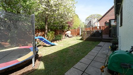 Back of house in Bramley Close, Sandford, with garden. Lawn and patio with decking behind, trampoline and slide