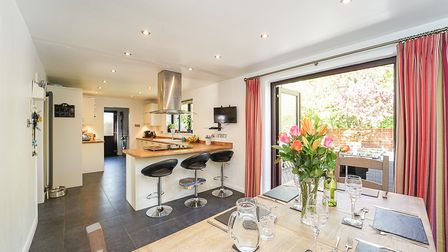 Modern kitchen-dining room with breakfast bar and three stools, dining table and bi-folding doors