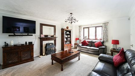 Lounge with black leather sofas, wooden coffee table, mantelpiece and radiator cover, window at back