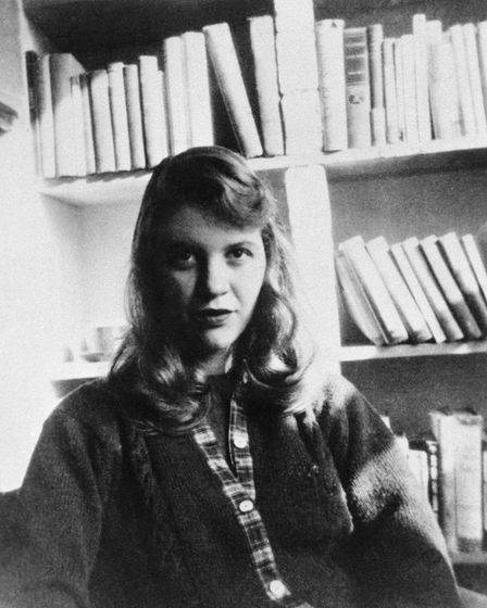 (Original Caption) Photo shows author Sylvia Plath seated in front of a bookshelf.