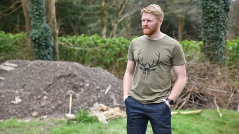 A man wears jeans and a t-shirt with a deer head design on the front. Behind him is a mound of earth and digging tools.