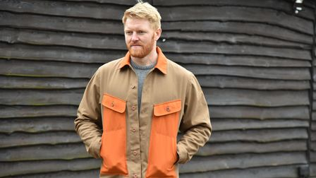 I chest and up shot of a man wearing a brown jacket with orange pockets. He stands in front of a barn.
