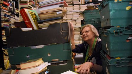Jenny Newton, manager of the Oxfam Books and Music shop in Bedford Street, dwarfed by the piles of b