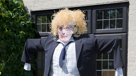 scarecrow wearing a suit erected outside of a house.