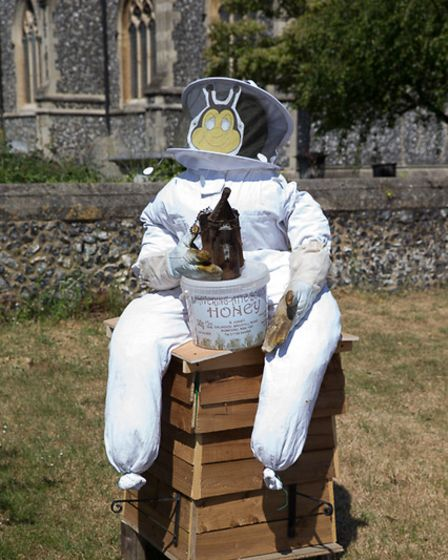 A scarecrow sat on a bee hive box with a bee keepers suit on