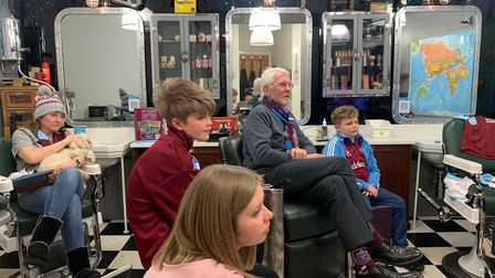 Burnley fans watch the Clarets in a locked-down barbers