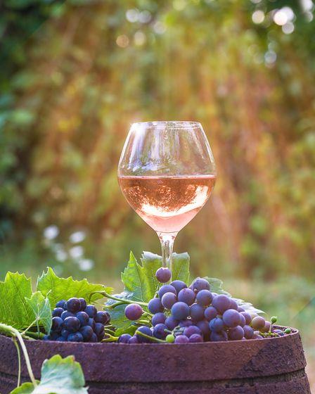 Glass of rose wine and red grapes with leaves on an old barrel