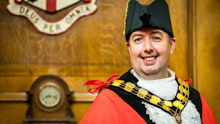 Cllr Troy Gallagher in mayoral robes standing in the mayor's parlour in Islington Town Hall, in front of the borough crest